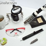 Top:Brass shavings in cup, helping hands with magnifying glass, Soldering iron with stand. Bottom:Solder wick, safety glasses, solder sucker solder.