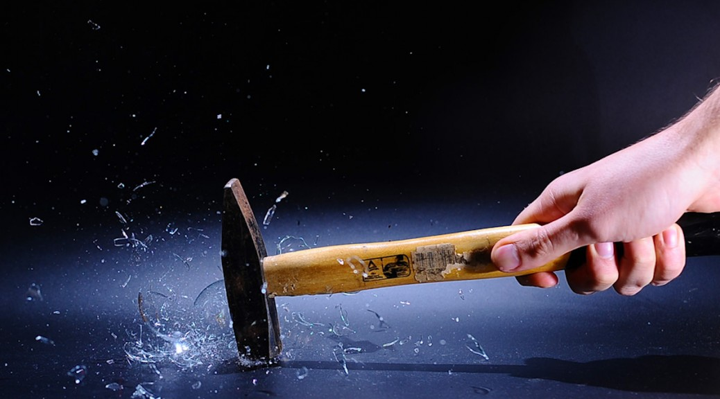 High speed photo of Lightbulb being smashed to bits by hammer.