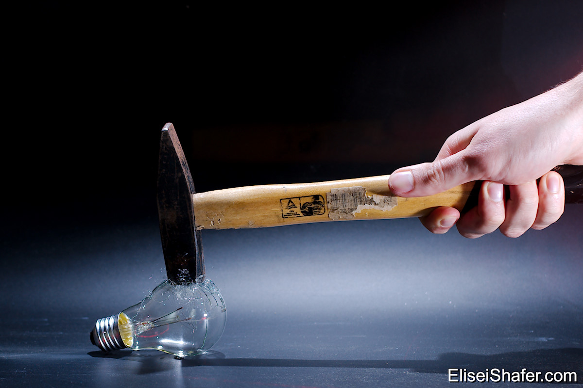High speed photo of light bulb being hit by hammer.